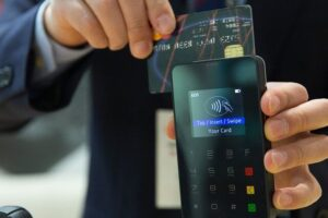 Negativação indevida - foto de um homem passando um cartão de crédito em uma máquina portátil.