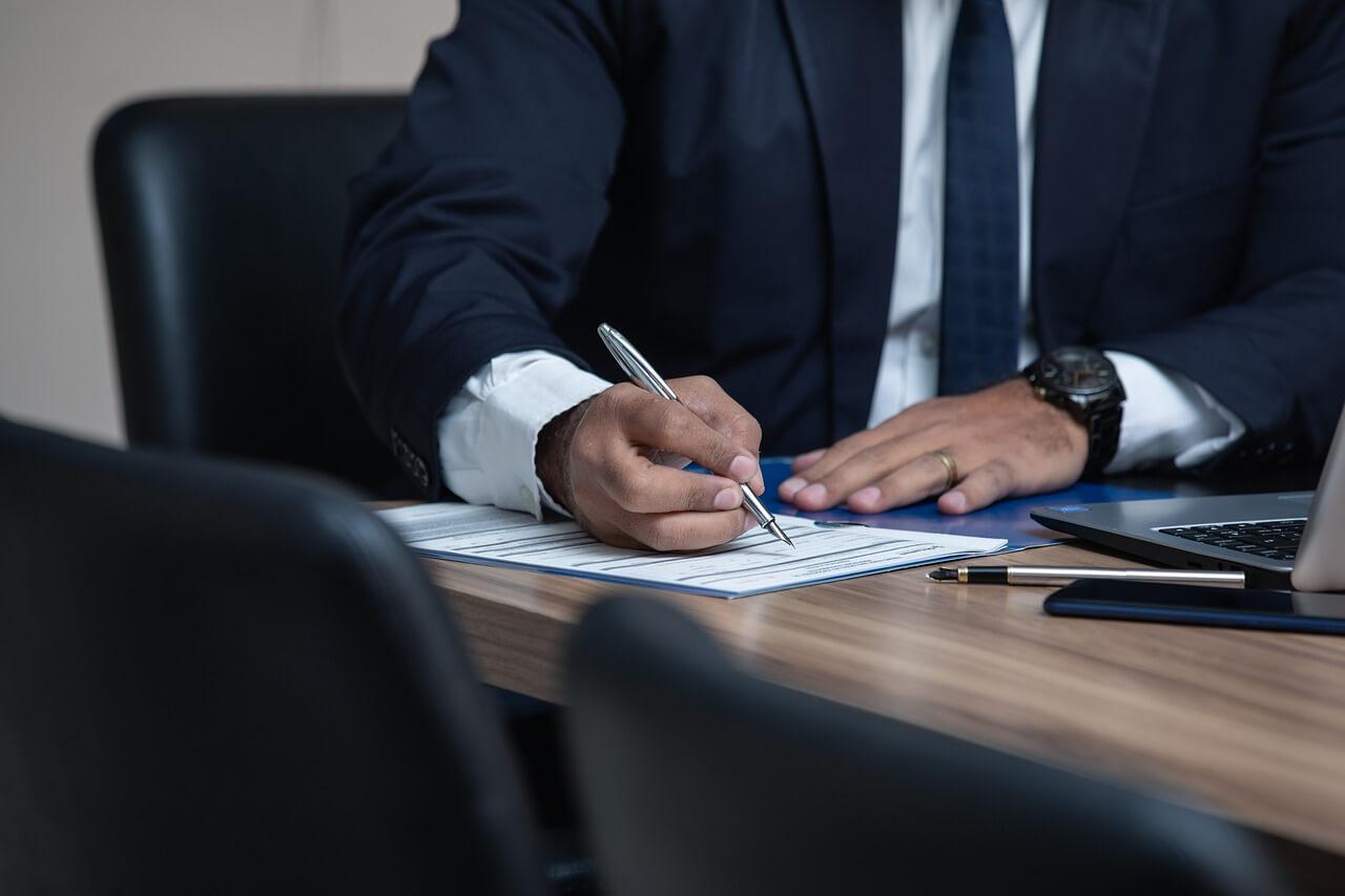 dano moral - foto de homem executivo, sentado em uma mesa, escrevendo em um papel com uma caneta tinteiro. Sobre a mesa, há um laptop.