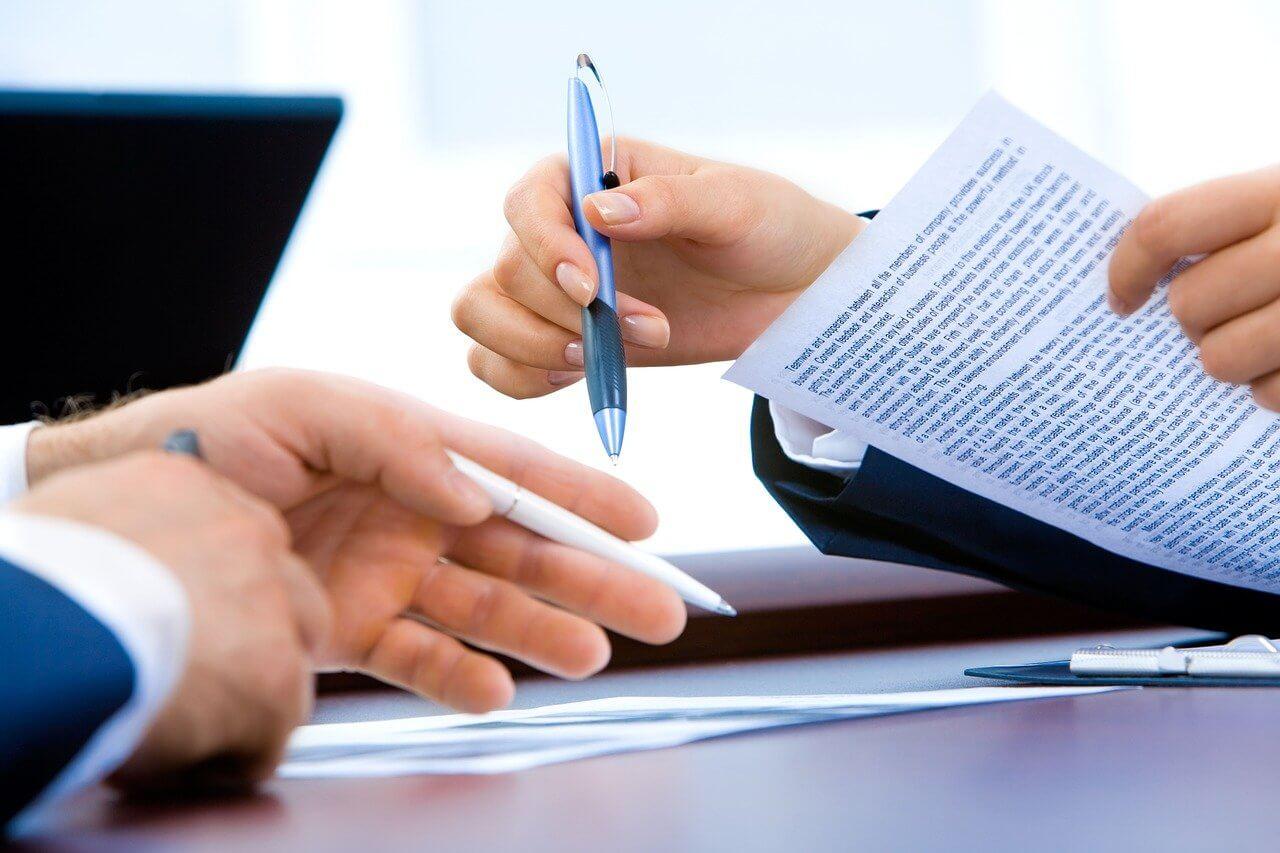 Inventário - mãos de dois executivos brancos, segurando canetas e papéis sobre uma mesa, ao lado de um laptop