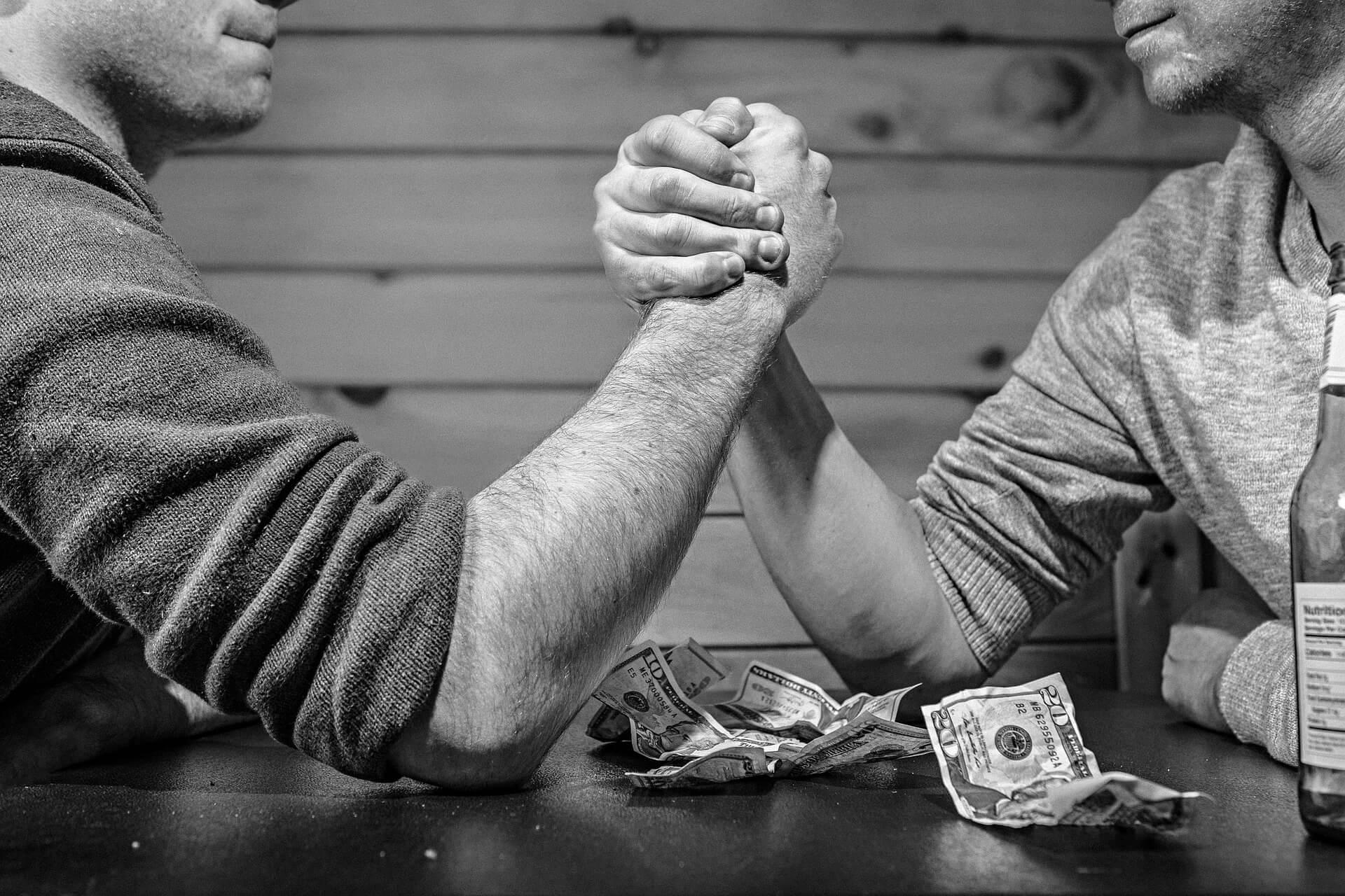 Foto em preto e branco, de dois homens brancos, disputando uma queda de braço sobre uma mesa de madeira escura e com algumas notas de dólares estadunidenses - Castanhari a indenizar Melhem 1