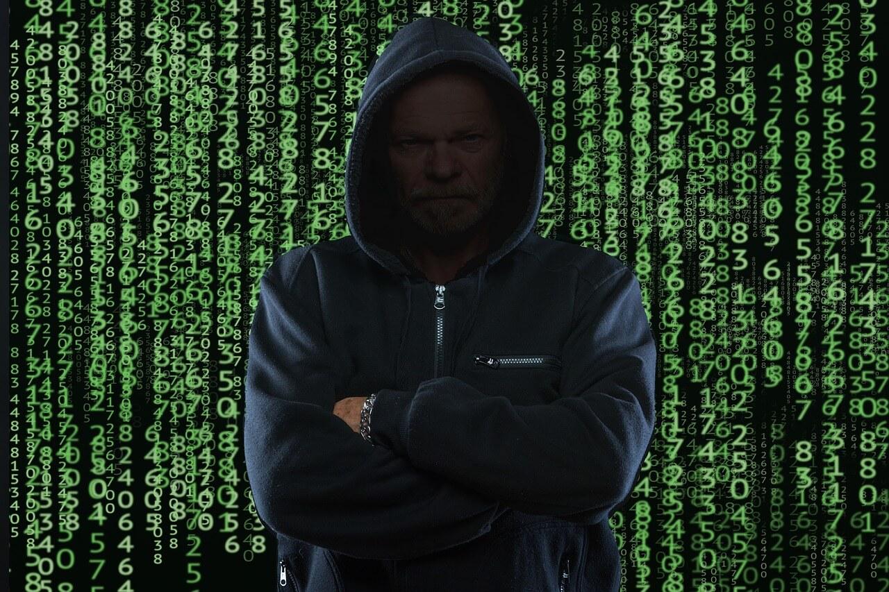 golpe bancário na internet - uma imagem de uma pessoa encapusada, sem aparecer seu rosto, e códigos de programação