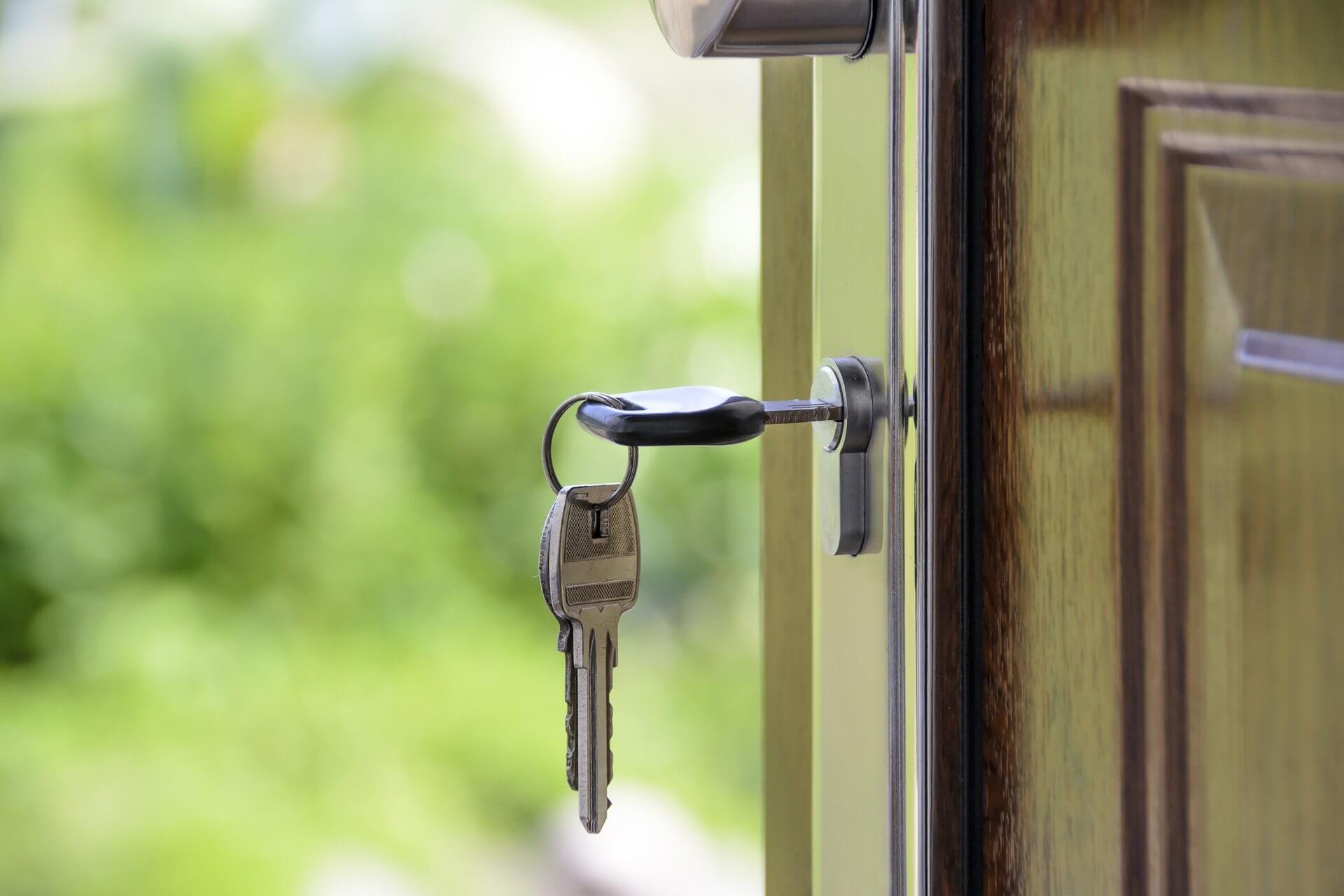 quem é o proprietário do imóvel - foto de uma chave em uma porta de entrada de madeira de uma casa.