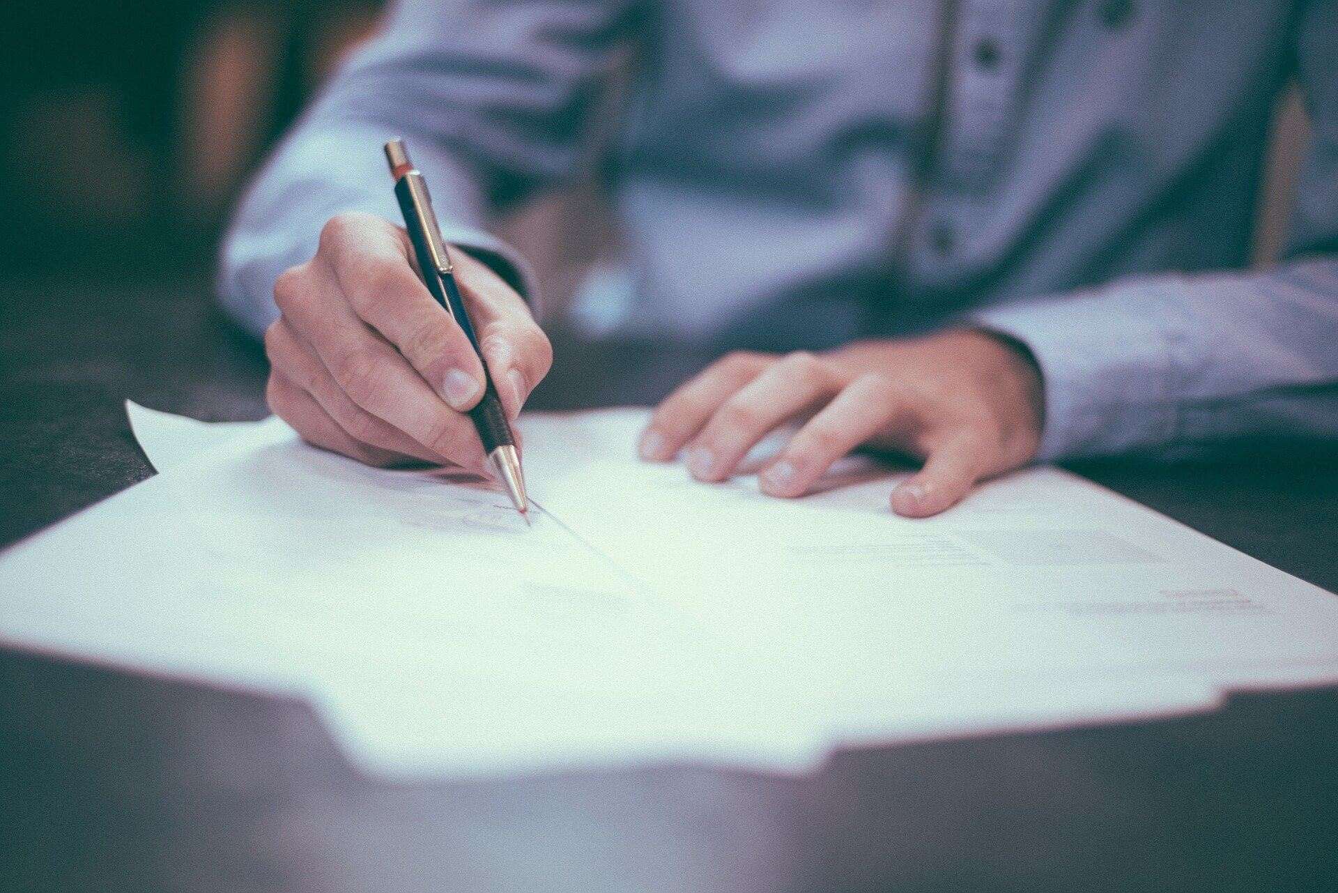 Inventário extrajudicial - foto de um homem branco, usando uma camisa social azul, assinando papéis sobre uma mesa de madeira escura.