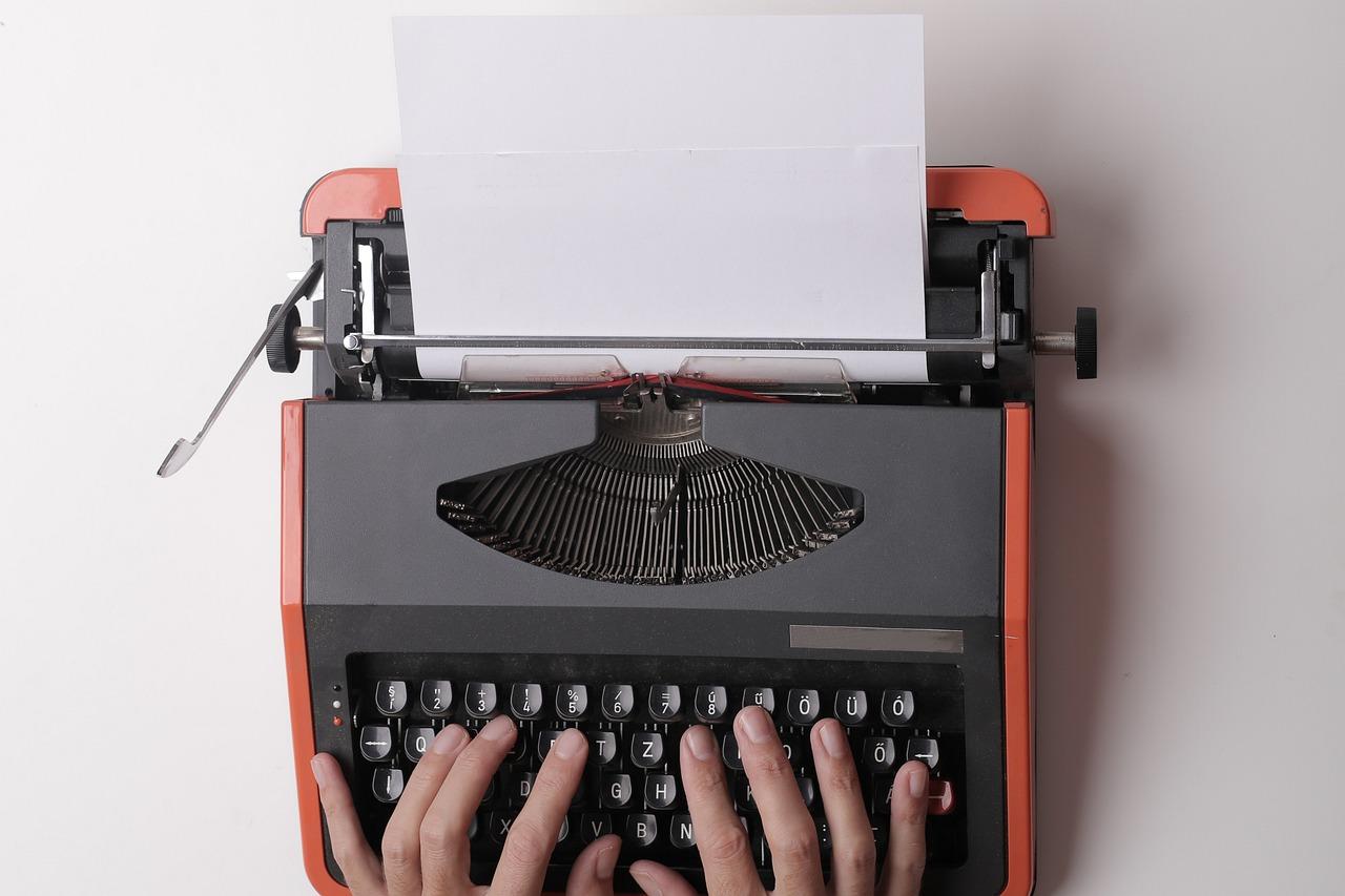 strikes por imagens com domínio público - imagem de uma mesa branca, com uma máquina escrever preta e laranja, com uma pessoa branca datilografando na máquina